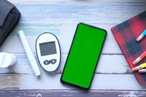 Smartphone und diabetische Messwerkzeuge auf hölzernem Hintergrund