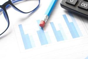 Finanzdiagramm, Taschenrechner und Notizblock auf dem Tisch foto