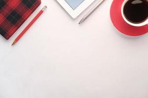 flache Komposition aus digitaler Tablette, Tee und Notizblock auf weißer Oberfläche