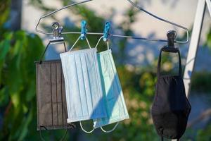 recycelte Gesichtsmasse auf Kleiderbügeln, die nach der Reinigung in der Sonne trocknen foto