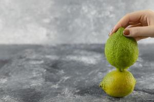Frauenhand, die zwei grüne frische Zitronen hält foto