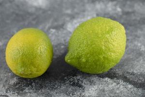 zwei grüne frische Zitronen auf einem Marmorhintergrund foto