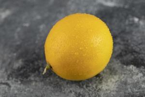 eine gelbe reife Zitrone auf einem Marmorhintergrund foto