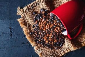 Kaffeebohnen, die aus einem roten Becher verschüttet werden foto