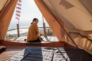 Frau sitzt außerhalb eines Zeltes foto