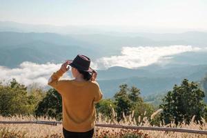 Frau in einem Hut auf einem Berggipfel foto