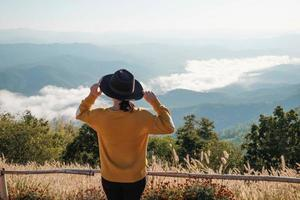 Frau sitzt mit einem Hut auf einem Berggipfel foto