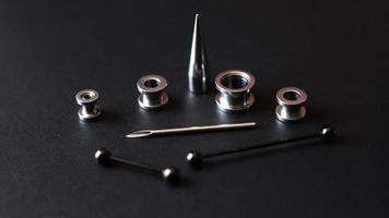 Satz Piercing-Werkzeuge auf einem dunklen Hintergrund foto