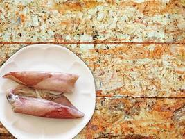 Tintenfisch auf weißem Teller auf hölzernem Tischhintergrund foto
