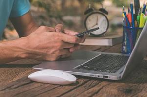 eine Person, die ein Smartphone vor einem Computer benutzt foto