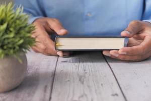 Mannhand, die ein Buch auf Tisch hält foto
