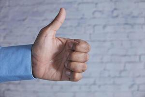 Männerhand hält einen Daumen hoch foto