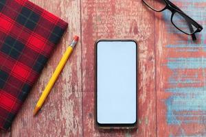 Draufsicht auf Smartphone und Notizblock auf dem Tisch