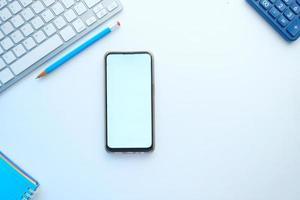 Draufsicht von Smartphone und Büro stationär auf weißem Hintergrund