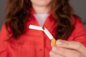 Frau hält eine kaputte Zigarette foto