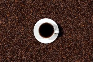 Draufsicht der weißen Kaffeetasse auf dem Kaffeebohnenhintergrund foto