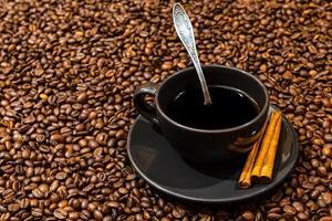 schwarze Kaffeetasse und Zimtstangen auf dem Kaffeebohnenhintergrund foto