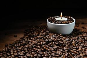 weiße Kaffeetasse voller Kaffeebohnen und brennender Kerze auf Kaffeebohnenstapel foto