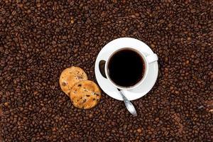 weiße Kaffeetasse und Kekse auf dem Kaffeebohnenhintergrund foto