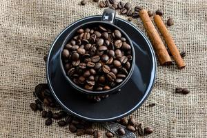 schwarze Kaffeetasse voller Bio-Kaffeebohnen und Zimtstangen auf Leinentuch foto