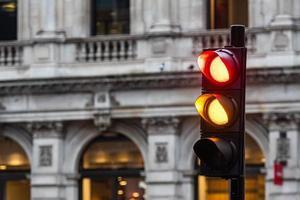 rote und orange Ampeln für Autos auf einem unscharfen Gebäudehintergrund foto