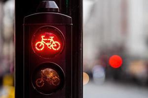 rotes Fahrrad-Verkehrszeichen mit unscharfem Stadthintergrund foto