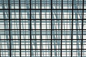 Metallgitter gegen eine graue Wand, der Schatten des Gitters foto