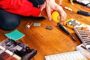 Person, die eine Holzoberfläche repariert foto