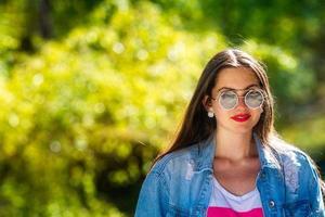 Außenporträt der schönen, emotionalen, jungen Frau in der Sonnenbrille foto