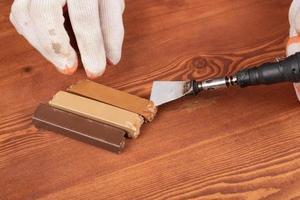 Person, die Holzlaminat restauriert foto