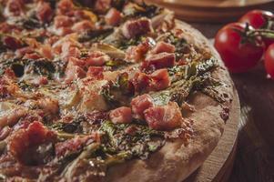 brasilianische Pizza mit Tomatensauce, Mozzarella, Endivien, Speck und Oregano foto