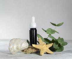 Braunglasflasche mit ätherischen Ölen oder Serumkosmetika mit Eukalyptusblättern, Muscheln und Seesternen foto