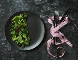 Diät-Salat von Salatblättern, Spinat und grünen Erbsen auf einem dunklen Hintergrund foto