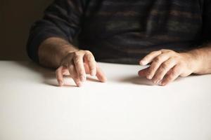 unerkennbarer Mann in einer vertrauten Position, der an einem weißen leeren Tisch sitzt foto