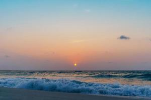 bunte Ozeanmeerwellen während eines Sonnenaufgangs oder Sonnenuntergangs mit der Sonne im Hintergrund foto