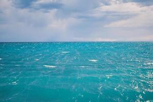 Seelandschaft mit klarer Horizontlinie und bewölktem Himmel foto