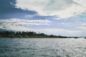 Sonnenliegen und Sonnenschirme am Ufer