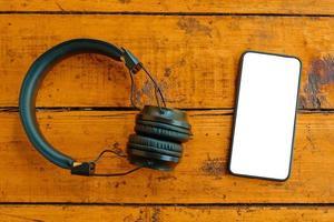 Draufsicht von Kopfhörern und Smartphone auf Holztisch