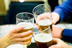 drei Leute klirren an Biergläsern foto