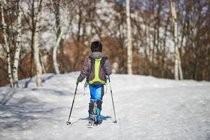 Junge mit Tourenskiern in der verschneiten Straße foto