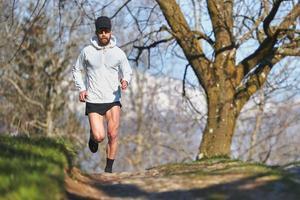 Mann läuft auf einem Naturlehrpfad foto