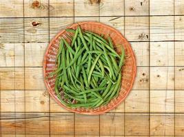 grüne Bohnen auf einem Weidenteller auf einem hölzernen Tischhintergrund foto
