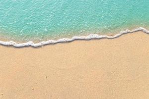 weiche Wellen mit Schaum des blauen Ozeans am Sandstrand foto