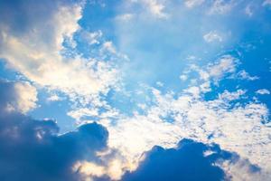 der Sonnenstrahl hinter den Wolken am blauen Himmel foto
