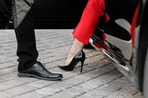 Nahaufnahme einer Frau in High Heels, die aus ihrem Auto steigt foto