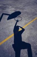 Mann Schatten auf dem Boden beim Basketball spielen foto