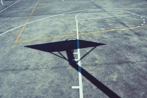 Straßenbasketballreifenschattenschattenbild auf dem Platz foto