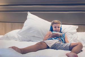 entspannter Junge mit Smartphone auf dem Bett foto