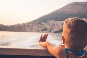 kleiner Junge, der mit dem Segelboot reist und bei Sonnenuntergang winkt foto