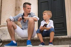 Vater und Sohn sitzen auf Stufen und entspannen sich in der Stadt foto